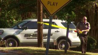 Police officer blocks off neighbourhood area of shooting
