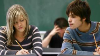 Un joven mirando el exámen de otra persona