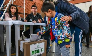 A boy helps his mother to vote in a polling station in Bogota during the first round of the presidential election in Colombia on May 27, 2018