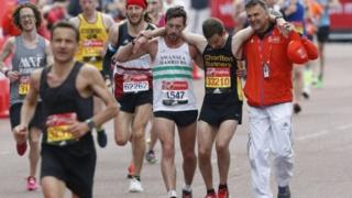 Matt Rees and a race volunteer assist David Wyeth over the finishing line of the London Marathon in 2017