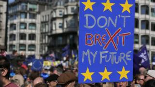Demonstrators hold placards as they prepare to participate in an anti Brexit, pro-European Union (EU) march in London on 25 March 2017