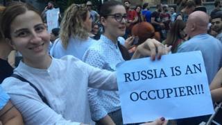 Ein Demonstrant hält ein Blatt Papier hoch und beschuldigt Russland, georgische Gebiete besetzt zu haben
