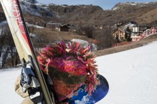A skier with a decorated helmet heads for the tracks