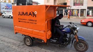 Un livreur regarde son téléphone assis sur un transporteur avec une publicité pour le site de commerce électronique nigérian Jumia à Abidjan.