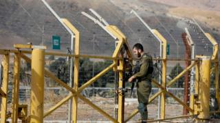 An Israeli soldier closes a border gate on the Israeli side of the border at the Jordan Valley site of Naharayim, also known as Baqura in Jordan, east of the Jordan river on November 10, 2019