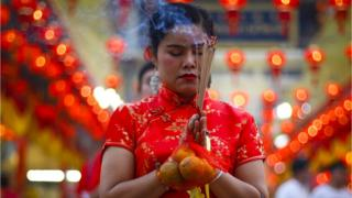 Worshippers burn incense in prayer at a temple to celebrate the Lunar New Year, or Spring Festival, in Chinatown in Bangkok, Thailand