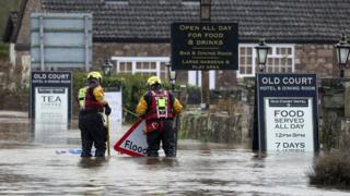 Rescue workers stand in floodwater that surrounds the village of Whitchurch in Herefordshire, after the River Wye burst its banks in the aftermath of Storm Dennis