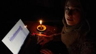 Mariam estudiando con su computadora a la luz de una vela