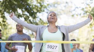 Mulher sorri e ergue os braços ao enconstar na linha de chegada de uma maratona