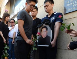 Family members and relatives hold a portrait of Zhang Chaolin outside the town hall in Aubervilliers, north-eastern suburbs of Paris, 14 August