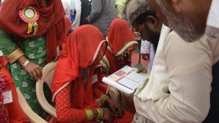 November 2016, an Indian bride listens as an officiator (2R) reads 'nikah ka certificate' or marriage certificate