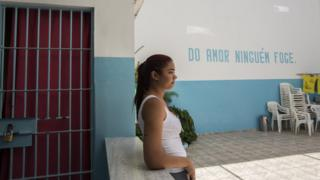 Tatiane Correia de Lima leans against a wall in the courtyard