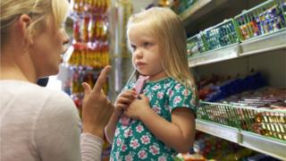 A child picking adult chocolate from a supermarket shelf