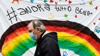 Un hombre pasa por delante de un cartel de apoyo en Italia