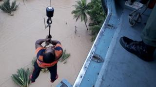 An Indian man being winched up to an Indian Air Force helicopter as he is evacuated from a flood affected area in the southern state of Kerala on 18 August