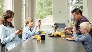 Família olhando o celular enquanto come