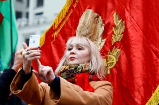 A woman takes a selfie with an image of Soviet state founder Vladimir Lenin.