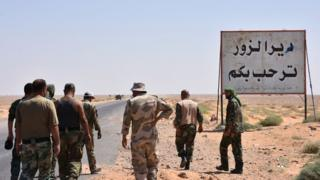 "Syrian government forces stand beside a sign saying ""Welcome to Deir al-Zour"" in eastern Syria on 3 September 2017"