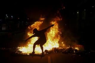 A young man practices a skateboarding move in front of a fire set by protestors following a demonstration against proposed federal government reforms on 15 March 2017 in Rio de Janeiro