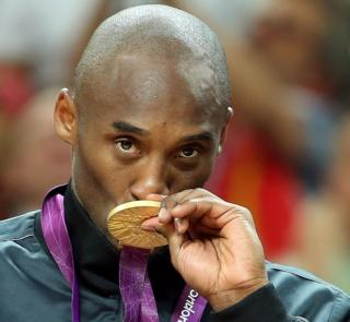 Kobe Bryant kissing gold medal at the Olympics.