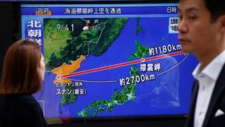 Orang-orang berjalan di depan TV Jepang yang menunjukkan jalur rudal.