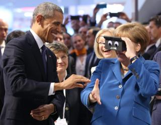 German Chancellor Angela Merkel tests a pair of virtual reality goggles with US President Barack Obama
