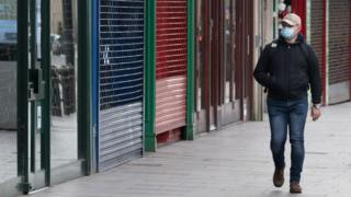 Man in mask walks past empty shops