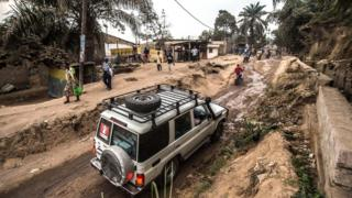 4x4 vehicle drives through dirt track with steep banks either side where pedestrians are walking