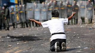 A demonstrator kneels down in front of security forces in Ureña, Venezuela