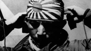 A Japanese kamikaze pilot tying on the honorary ribbons that were always worn when on a suicide mission. 'Kamikaze', which means 'winds of the gods', were pilots who deliberately crashed their bomb laden planes onto American warships during the Second World War.