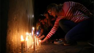People place candles outside the Instituto Politecnico, a technical high school, where the five Argentine citizens who were killed in the truck attack in New York on October 31 went to school, in Rosario, Argentina November 1, 2017