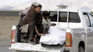 タリバンによるカンダハル空港襲撃後、男性たちが遺体を運ぶ(9日)