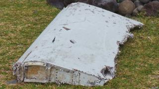 French gendarmes and police stand near a large piece of plane debris which was found on the beach in Saint-Andre, on the French Indian Ocean island of La Reunion, July 29, 2015.