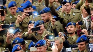 Soldiers hold their camera phones up and take pictures