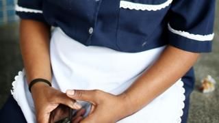 Woman in maid's uniform holding mobile phone