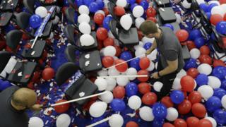 Workers pop balloons during cleanup after the final day of the Democratic National Convention
