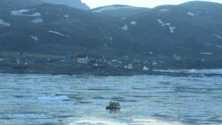 Rescuers use a life raft to search for the missing after a tsunami hit the village of Nuugaatsiaq, northwestern Greenland