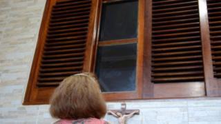 Mulher faz prece a imagem de santa em vidro superior da janela