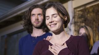 Amanda Knox, eyes closed, smiles and clasps her hands over her heart, while her fiance, a bearded and long-haired young man, places a hand on her shoulder