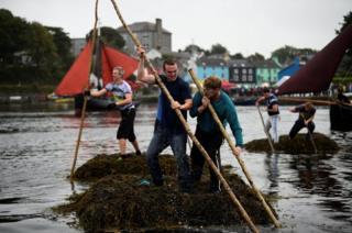 Los participantes de una carrera de balsas hechas con algas en Kinvara, Irlanda.