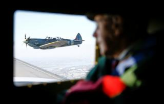 in_pictures A WWII Spitfire can be seen out of the window of a C47 A Dakota plane, while war veteran Roy Briggs looks on, during Remembrance Sunday commemorations in Dover.