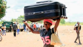A woman carries a suitcase on her head at the border post of Chissanda in Dundo on the Angola and DR Congo border - Saturday 20 October 2018