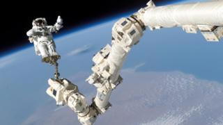 An astronaut suspended by an arm above the surface of planet Earth.