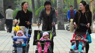Chinese mums pushing babies in a pram.