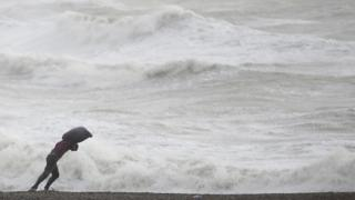A man leans into the wind on the beach at Newhaven, southern England