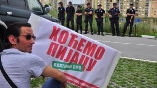 """Jedan od demonstranata drži transparent na kome piše """"Hoćemo pijacu"""", dok se sedam policajaca vidi u pozadini"""