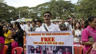 """A man displays a placard as others sing Myanmar national anthem during a protest rally against a Thai court""""s verdict sentencing two Myanmar migrant workers to death, in Yangon, Myanmar, Tuesday, Dec. 29 2015"""
