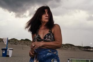 Woman under grey clouds on a beach