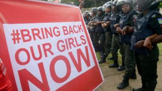 Supporters of the #BringBackOurGirls campaign hold a placard as policewomen block supporters from marching to the president's official residence in Abuja on October 14, 2014.