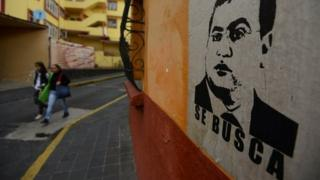 """Women walk by a poster depicting outgoing Veracruz Governor Javier Duarte with the word """"Wanted"""" at a neighbourhood in Xalapa, Mexico, October 25, 2016."""